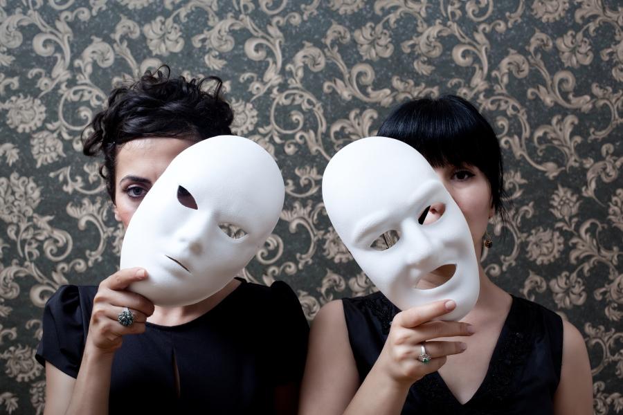 Two women peeking behind mask on wallpaper background