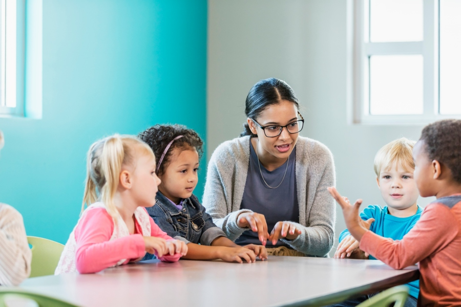 Multi-ethnic preschool teacher and students in classroom